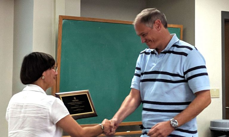 Department of Chemistry chair Judith Burstyn presents professor Shannon Stahl with a plaque for receiving the prestigious Steenbock Professorship.