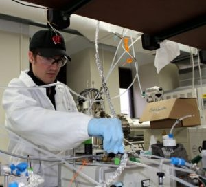 Sean Staudt, a graduate student who works with CAICE, adjusts the flow of dinitrogen pentoxide to a mass spectrometer used to study reactions of the atmospheric gas at atmospheric interfaces.