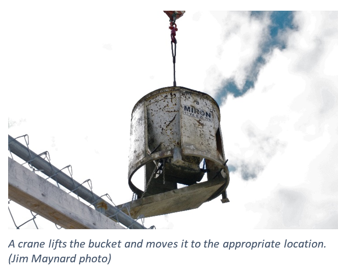 A crane lifts the bucket and moves it to the appropriate location.