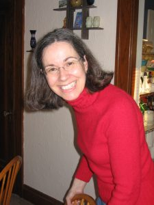 woman in red shirt with glasses, smiling