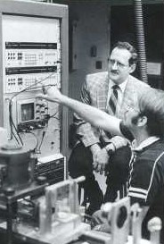 Two men work on equipment in a lab