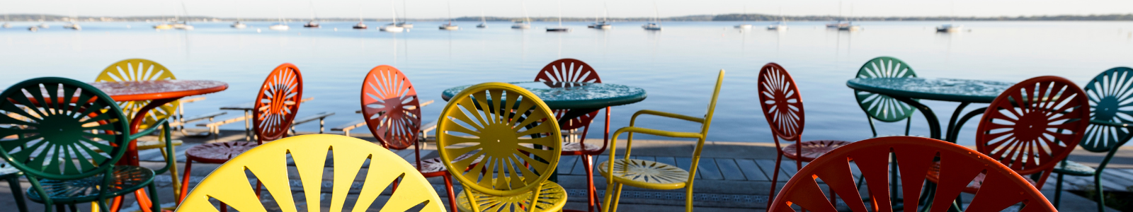 brightly colored chairs in front of a lake