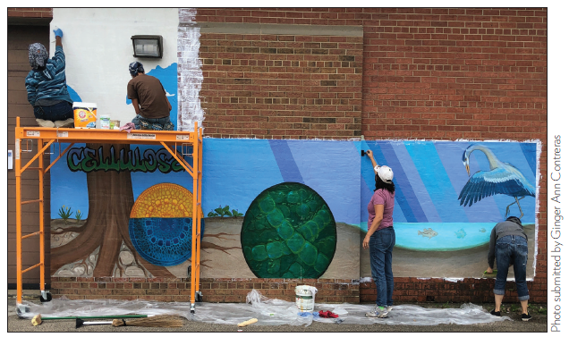 People painting a mural on a red brick wall