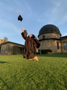 Person on the grass jumping in the air with graduation cap and gown on. Tossing graduation cap into the air mid jump.