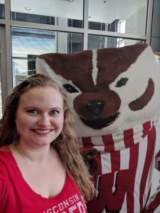 Person smiling and standing next to Bucky Badger cardboard cutout